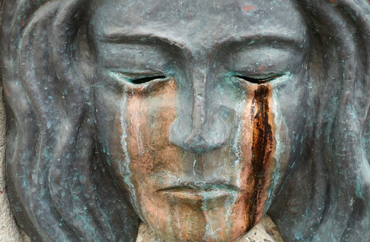 gray sculpture of a woman with closed eyes where the path of tears are brozen and rusted